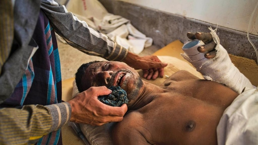 A Bangladeshi man wipes the face of one of the workers injured in the collapse of a cement factory roof, after he is brought in for treatment at the Khulna Medical Hospital in Khulna, Bangladesh, Thursday, March 12, 2015. About 150 workers were on duty when the roof of a five-story cement factory under construction collapsed Thursday at Mongla in Bagerhat district. (AP Photo/Shaikh Mohir Uddin)