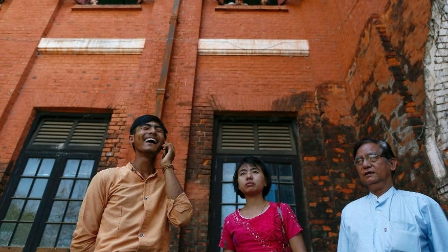 Student protester Thant Lwin Wai Chit, left, speaks on a mobile phone as his sister, center, and father stand by outside the court house after his release in Tharyarwaddy, north of Yangon, Myanmar, Thursday, March 12, 2015. Authorities freed several students detained after a bloody protest crack-down, but others involved in the stand-off over a new education law will face charges which carries up to two-year prison term. (AP Photo/Gemunu Amarasinghe)