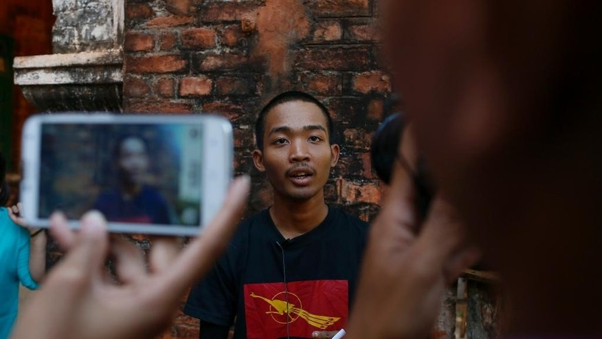 Student protester Kyaw Zin Thant speaks to journalists outside a court house after his release in Tharyarwaddy, north of Yangon, Myanmar, Thursday, March 12, 2015. Authorities freed several students detained after a bloody protest crack-down, but others involved in the stand-off over a new education law will face charges which carries up to two-year prison term. (AP Photo/Gemunu Amarasinghe)
