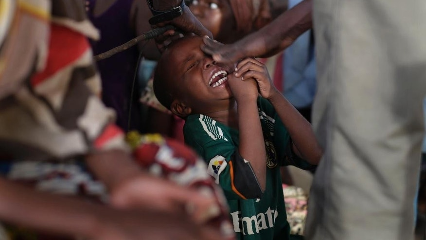 A young boy cries after being inadvertently hit in the eye by the teacher's whip as young girls recite   verses of the quran in a makeshift madrasa in the Zafaye refugee camp, some 15 kms (10 miles) from downtown N'djamena, Chad, Wednesday March 11, 2015. Over 5000 refugees of Chadian descent who fled the fighting in Central African Republic have been living in the camp for over a year.  Chad is also hosting thousands of refugees fleeing the current Boko Haram fighting in Nigeria. (AP Photo/Jerome Delay)