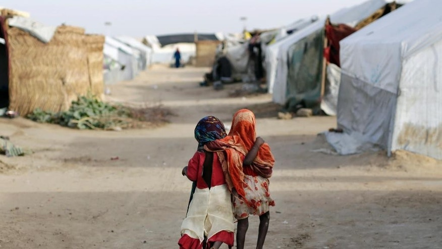 AP10ThingsToSee - Ami and Ashbu, both three-years-old, walk  arm in arm  in the Zafaye refugee camp, some 15 kms (10 miles) from downtown N'djamena, Chad, Wednesday March 11, 2015.  (AP Photo/Jerome Delay)