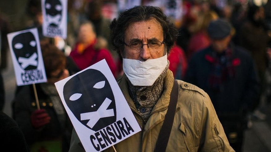 "In this Sunday, Jan. 25, 2015 file photo, a demonstrator marches with his mouth covered and carries a placard that reads: ""Censorship"" during a protest against Spanish Citizens Security Law in Madrid. Spain's senate is set Wednesday to approve a tough new security law that includes stiff fines for people who take part in violent anti-austerity protests.  (AP Photo/Andres Kudacki, File)"