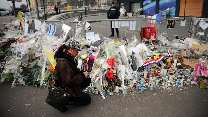 FILE - This Wednesday, Jan. 20, 2015, file picture shows a woman lighting a candle outside the kosher grocery where Amedy Coulibaly killed four people in a terror attack, in Paris, France. Two men with ties to one of the three gunmen who terrorized Paris were handed preliminary terrorism charges on Friday, the Paris prosecutor said, describing hundreds of texts, regular meetings, and DNA recovered from a stun gun among belongings inside a bloodied kosher supermarket.  (AP Photo/Christophe Ena, File)