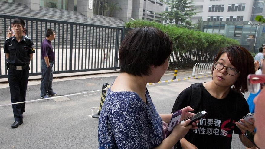In this photo taken Thursday, July 31, 2014, women's rights activist Wei Tingting, right, waits outside a court where the first court case in China involving so-called conversion therapy is held in Beijing, China. Wei is one of five women activists criminally detained for planning to put up anti-sexual harassment posters in three Chinese cities according to her lawyer on Friday, March 13, 2015. (AP Photo/Ng Han Guan)