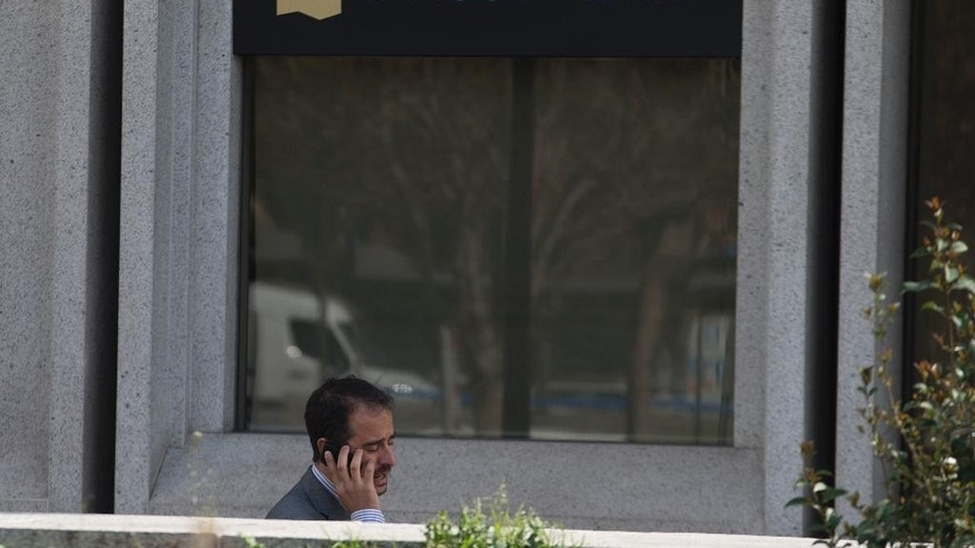 A man speaks on a cell phone outside a Banco Madrid office in Madrid, Spain, Thursday, March 12, 2015. The entire board of Spain's Banco de Madrid bank catering to wealthy clients has resigned after its Andorran owner was accused by the U.S. of money laundering for clients from China, Russia and Venezuela, Banco de Madrid said Thursday. (AP Photo/Paul White)