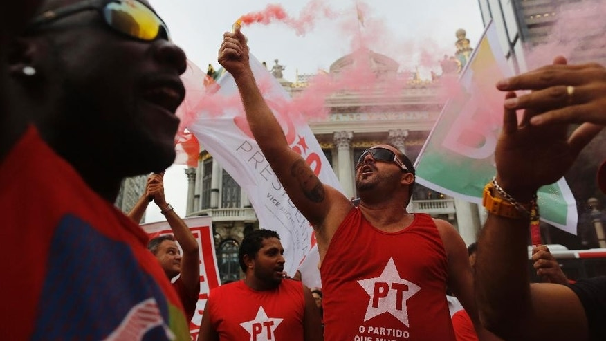 Demonstrators wearing Workers Party t-shirts hold flares and shout slogans during a protest in support of the state-run oil company Petrobras in Rio de Janeiro, Brazil, Friday, March 13, 2015. Brazilian unions and backers of President Dilma Rousseff marched Friday in several cities across the nation, mostly to show support for state-run oil company Petrobras as it's engulfed by a corruption scandal, but also to back Rousseff. (AP Photo/Leo Correa)