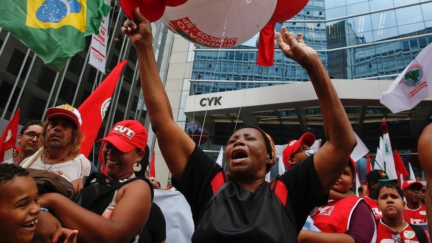 Demonstrators gather for a march in support of the state-run oil company Petrobras and Brazil's President Dilma Rousseff, outside the Petrobras office building, in Sao Paulo, Brazil, Friday, March 13, 2015. Brazilian unions and backers of President Dilma Rousseff marched Friday in several cities across the nation, mostly to show support for state-run oil company Petrobras as it's engulfed by a corruption scandal. (AP Photo/Andre Penner)