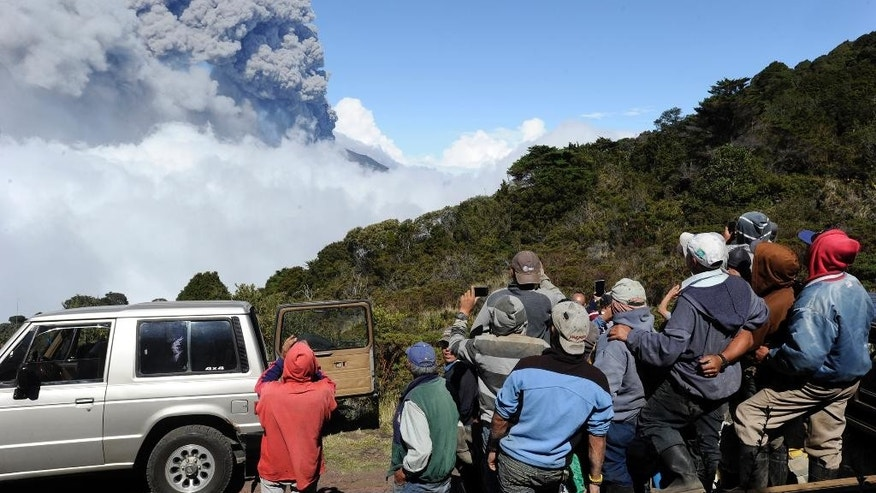 People watch column of ash and smoke erupting from the Turrialba volcano in Turrialba, Costa Rica, Thursday, March 12, 2015. The volcano erupted three times Thursday and state observers recorded a smaller eruption Friday morning. Costa Rican officials have closed the country's principle airport in the capital of San Jose after the eruption filled the sky with ash. The country's public education ministry suspended classes Friday at 12 schools near the volcano. (AP Photo/Grupo Nacion, Alonso Tenorio)