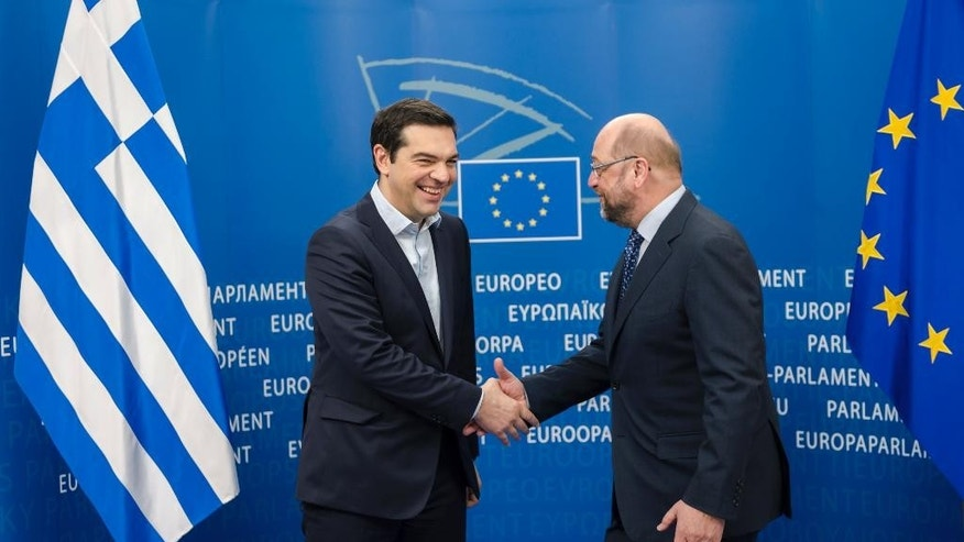 European Parliament President Martin Schulz, right, welcomes Greece's Prime Minister Alexis Tsipras upon his arrival at the European Parliament in Brussels Friday, March 13, 2015. (AP Photo/Geert Vanden Wijngaert)