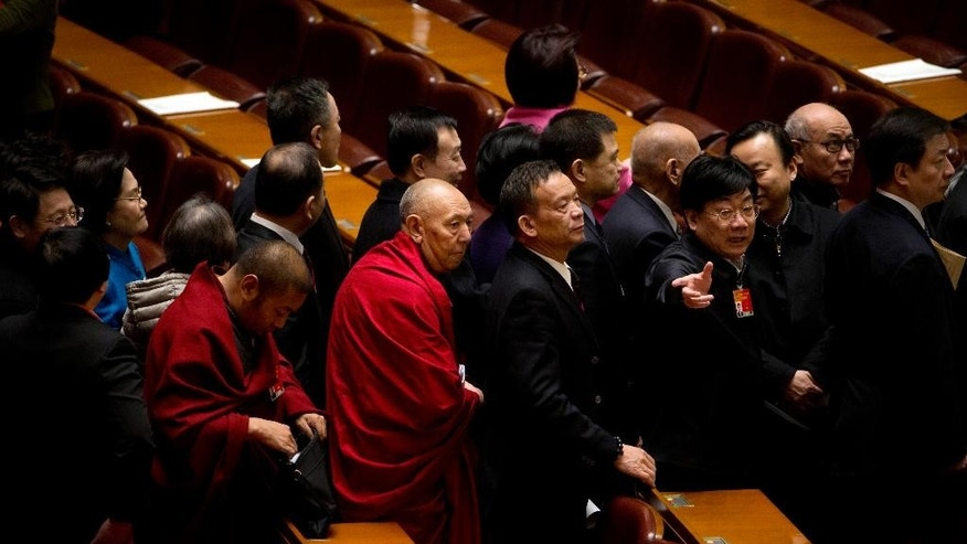 In this March 10, 2015 photo, Tibetan delegates leave the Great Hall of the People following a plenary session of the Chinese People's Political Consultancy Conference in Beijing. China's ruling Communist Party is eager to have the Dalai Lama's successor firmly under its influence, and officials during this week's annual national congress expressed dismay over his recent comments that he might not be reincarnated. (AP Photo/Mark Schiefelbein)