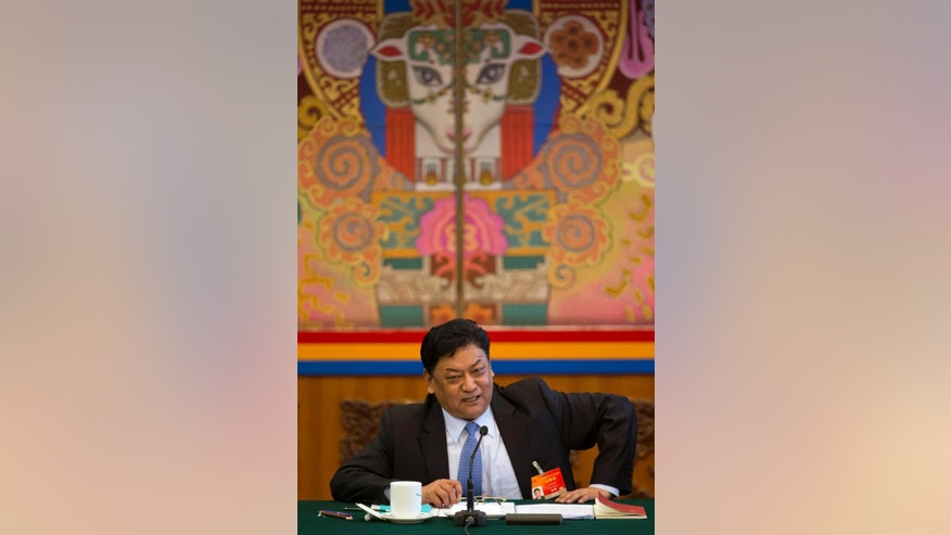 In this March 9, 2015 photo, Padma Choling, head of the Tibet Autonomous Region People's Congress answers a question during a briefing on the sideline of the National People's Congress in Beijing's Great Hall of the People. China's ruling Communist Party is eager to have the Dalai Lama's successor firmly under its influence, and officials during this week's annual national congress expressed dismay over his recent comments that he might not be reincarnated. (AP Photo/Ng Han Guan)