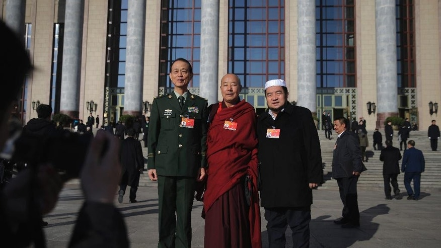 In this March 10, 2015 photo, a Tibetan monk, center, poses with other delegates for photos outside the Great Hall of the People ahead of a plenary session of the Chinese People's Political Consultative Conference (CPPCC) in Beijing. China's ruling Communist Party is eager to have the Dalai Lama's successor firmly under its influence, and officials during this week's annual national congress expressed dismay over his recent comments that he might not be reincarnated. (AP Photo/Andy Wong)