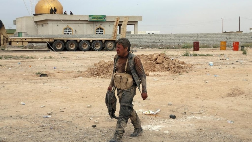 A Shiite militiaman returnes from a battle against Islamic State extremists at Camp Speicher, the front line in Tikrit, 80 miles (130 kilometers) north of Baghdad, Iraq, Thursday, March 12, 2015. Rockets and mortars echoed across Saddam Hussein's hometown of Tikrit on Thursday as Iraqi security forces clashed with Islamic State militants a day after sweeping into the Sunni city north of Baghdad. (AP Photo/Khalid Mohammed)