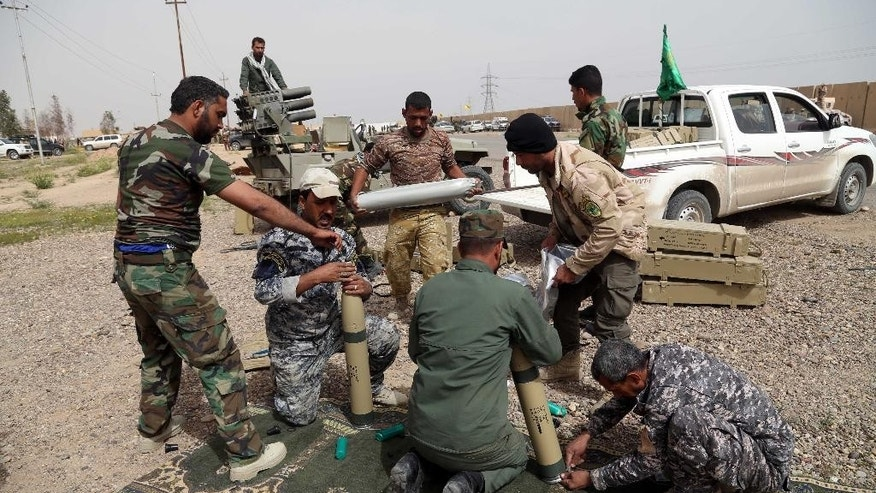 Members of an Iraqi Shiite militant group called Soldiers of Imam Ali Brigades prepare to launch rockets against Islamic State extremists' positions in Qadisiyya neighborhood in Tikrit, 80 miles (130 kilometers) north of Baghdad, Iraq, Friday, March 13, 2015. Iraqi forces entered Tikrit for the first time on Wednesday from the north and south. On Friday, they fought fierce battles to secure the northern Tikrit neighborhood of Qadisiyya and lobbed mortars and rockets into the city center, still in the hands of IS. Iraqi military officials have said they expect to reach the center of Tikrit within two to three days. (AP Photo/Khalid Mohammed)