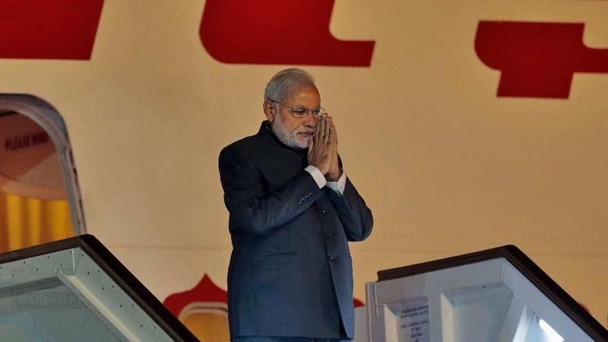 India's Prime Minister Narendra Modi gestures as he disembarks from a plane upon his arrival in Colombo, Sri Lanka, Friday, March 13, 2015. Modi's three-day visit to Sri Lanka reflects a bounce back in bilateral relations, as India seeks to mitigate China's growing influence at New Delhi's doorstep. The two sides are expected to discuss expanding trade, Sri Lanka's post-war rehabilitation and reconciliation as well as the most contentious issue of poaching. (AP Photo/Eranga Jayawardena)