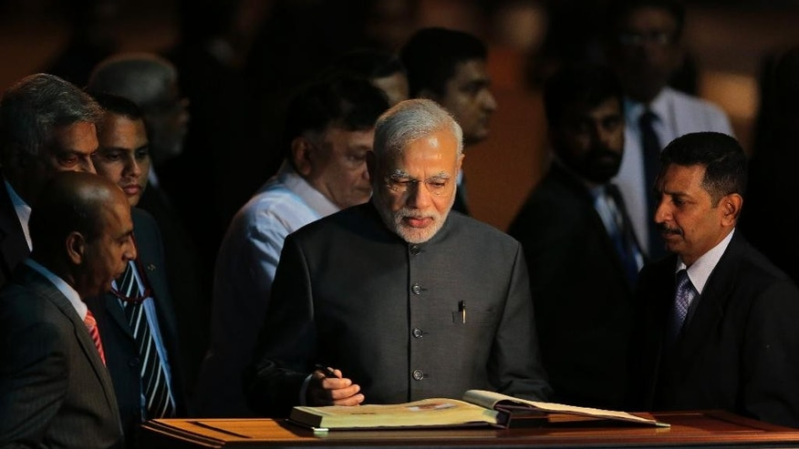 India's Prime Minister Narendra Modi, center, signs the visitor's book upon his arrival in Colombo, Sri Lanka, Friday, March 13, 2015. Modi's three-day visit to Sri Lanka reflects a bounce back in bilateral relations, as India seeks to mitigate China's growing influence at New Delhi's doorstep. The two sides are expected to discuss expanding trade, Sri Lanka's post-war rehabilitation and reconciliation as well as the most contentious issue of poaching. (AP Photo/Eranga Jayawardena)