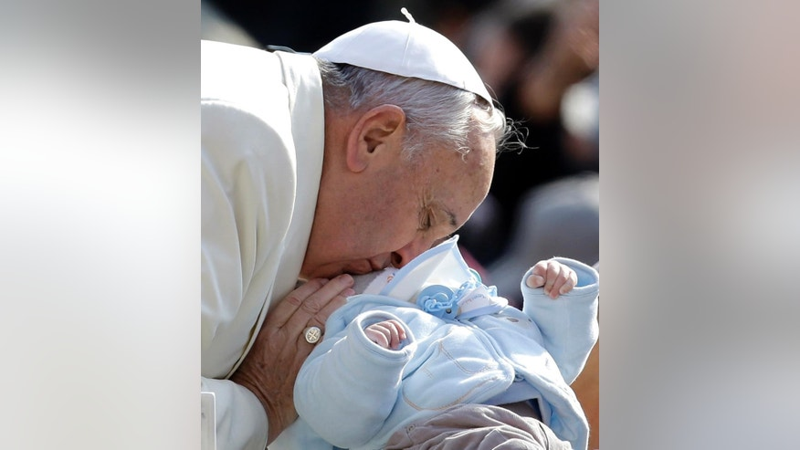 AP10ThingsToSee - Pope Francis kisses a baby as he arrives for his weekly general audience in St. Peter's Square, at the Vatican, Wednesday, March 11, 2015. (AP Photo/Gregorio Borgia)