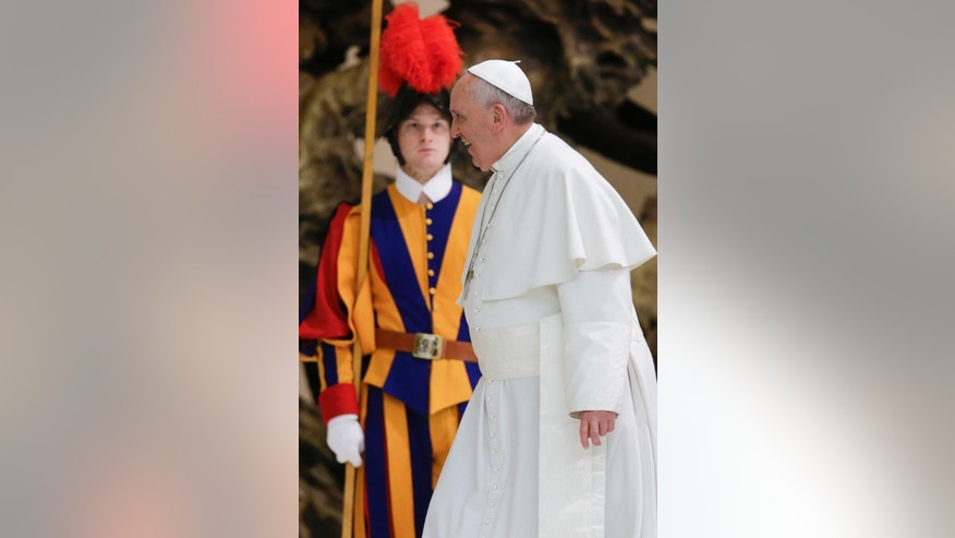 Pope Francis walks past a Swiss guard as he arrives for a private audience with participants to the course promoted by the Penitentiary Apostolic Tribunal, in the Paul VI hall at the Vatican,  Thursday, March 12, 2015. (AP Photo/Andrew Medichini)
