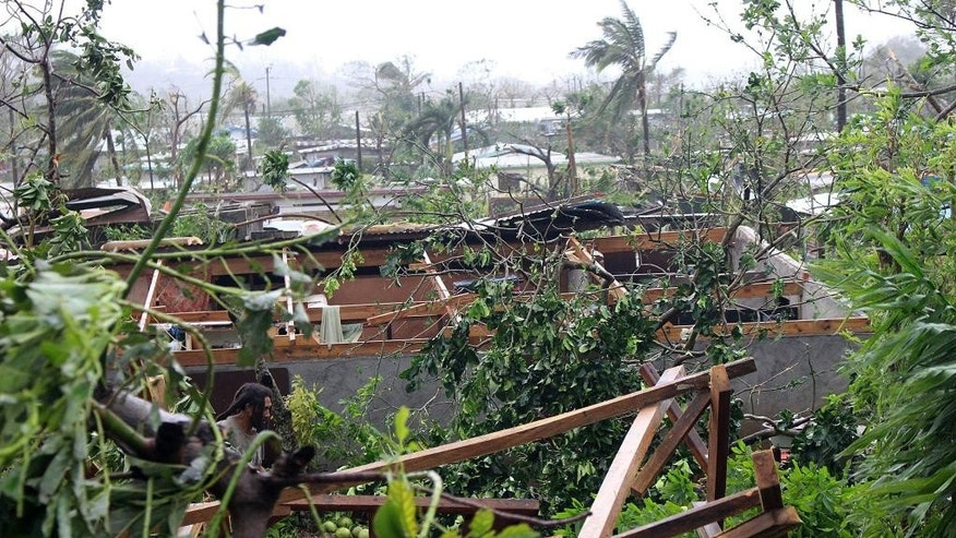In this photo provided by non-governmental organization 350.org, debris is scattered over a building in Port Vila, Vanuatu, Saturday, March 14, 2015, in the aftermath of Cyclone Pam. Winds from the extremely powerful cyclone that blew through the Pacific's Vanuatu archipelago are beginning to subside, revealing widespread destruction. (AP Photo/350.org, Isso Nihemi ) EDITORIAL USE ONLY, NO SALES
