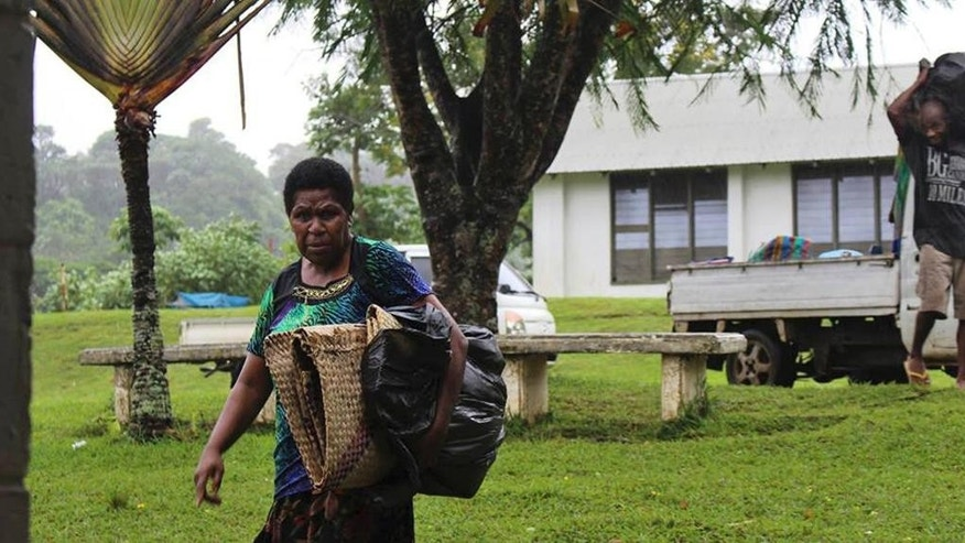 In this photo provided by non-profit organization 350.org,  a woman, left, and man gather items in Port Vila, Vanuatu, Saturday, March 14, 2015, in the aftermath of Cyclone Pam.  Winds from the extremely powerful cyclone that blew through the Pacific's Vanuatu archipelago are beginning to subside, revealing widespread destruction. (AP Photo/350.org, Isso Nihemi ) EDITORIAL USE ONLY, NO SALES