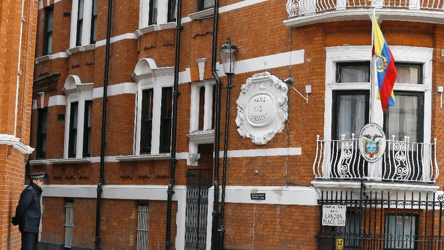 A police officer stands  outside of the Ecuadorean embassy in London, Friday, March 13, 2015. Swedish prosecutors on Friday offered to travel to London to question WikiLeaks founder Julian Assange, who has been living at the Ecuadorean embassy in London since 2012, potentially breaking a stalemate in an almost five-year-old investigation into alleged sex crimes, (AP Photo/Kirsty Wigglesworth)