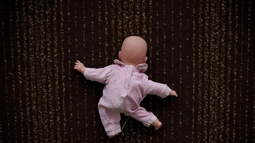 In a picture taken on Saturday, March 7, 2015, a doll lies on the floor of a children's home, in Khartsyzk, Ukraine. A brutal conflict between Russia-backed rebels and Ukrainian government troops has affected more than 1.7 million children on both sides of the front line, according to the UN's children's agency, with some of them sent to orphanages when their parents got killed or went to fight for the rebels, while some parents gave up their foster children because they were no longer receiving benefits for them. (AP Photo/Vadim Ghirda)