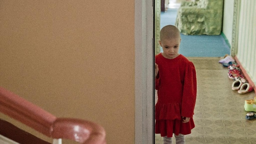 In a picture taken on Saturday, March 7, 2015, Veronika stands in the doorway of the girls room at a children's home, in Khartsyzk, Ukraine. A brutal conflict between Russia-backed rebels and Ukrainian government troops has affected more than 1.7 million children on both sides of the front line, according to the UN's children's agency, with some of them sent to orphanages when their parents got killed or went to fight for the rebels, while some parents gave up their foster children because they were no longer receiving benefits for them. (AP Photo/Vadim Ghirda)