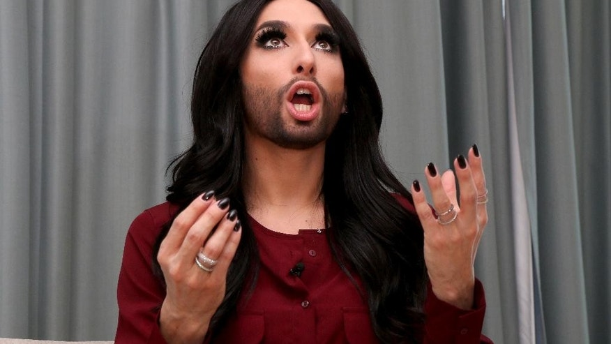 In this March 9, 2015 photo,  Conchita Wurst, Austrian winner of the Eurovision Song Contest 2014, attends an interview with The Associated Press in Vienna, Austria. Long legs crossed, one leopard-skin patterned spike heel dangling, the bearded diva with the expressive brown eyes leans back and laughs a throaty laugh when asked what has changed for her since winning Europe's biggest entertainment contest nearly a year ago. (AP Photo/Ronald Zak)