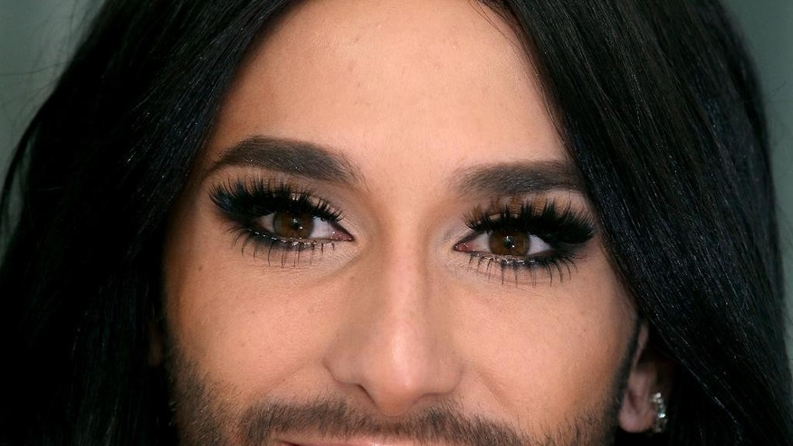 In this March 9, 2015 photo,  Conchita Wurst, Austrian winner of the Eurovision Song Contest 2014 poses, during an interview with The Associated Press in Vienna, Austria. Long legs crossed, one leopard-skin patterned spike heel dangling, the bearded diva with the expressive brown eyes leans back and laughs a throaty laugh when asked what has changed for her since winning Europe's biggest entertainment contest nearly a year ago. (AP Photo/Ronald Zak)