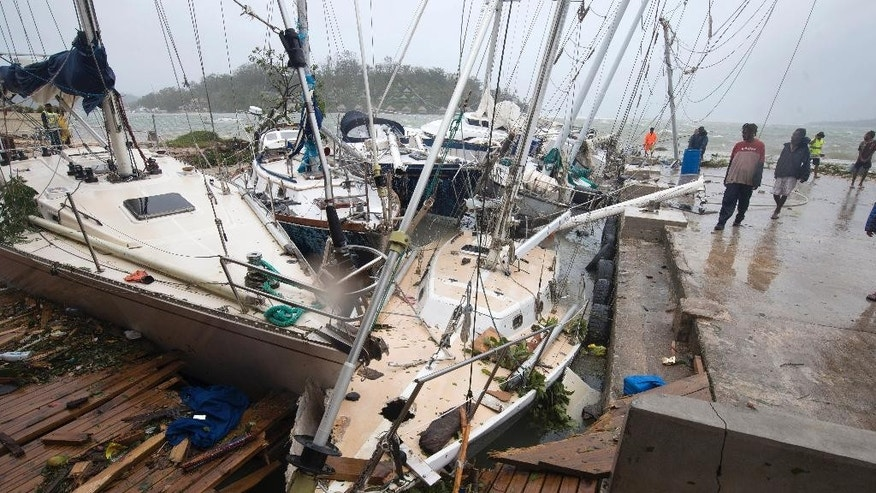 In this image provided by UNICEF Pacific, people on a dock view yachts damaged in Port Vila, Vanuatu, Saturday, March 14, 2015, in the aftermath of Cyclone Pam. Winds from the extremely powerful cyclone that blew through the Pacific's Vanuatu archipelago are beginning to subside, revealing widespread destruction. (AP Photo/UNICEF Pacific, Humans of Vanuatu) EDITORIAL USE ONLY, NO SALES