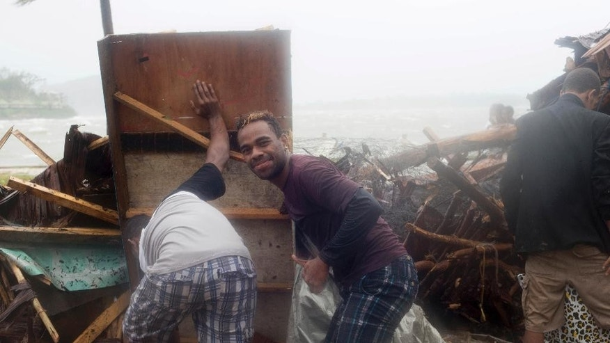 In this image provided by UNICEF Pacific, people scour through debris damaged and flung around in Port Vila, Vanuatu, Saturday, March 14, 2015, in the aftermath of Cyclone Pam. Winds from the extremely powerful cyclone that blew through the Pacific's Vanuatu archipelago are beginning to subside, revealing widespread destruction. (AP Photo/UNICEF Pacific, Humans of Vanuatu) EDITORIAL USE ONLY, NO SALES