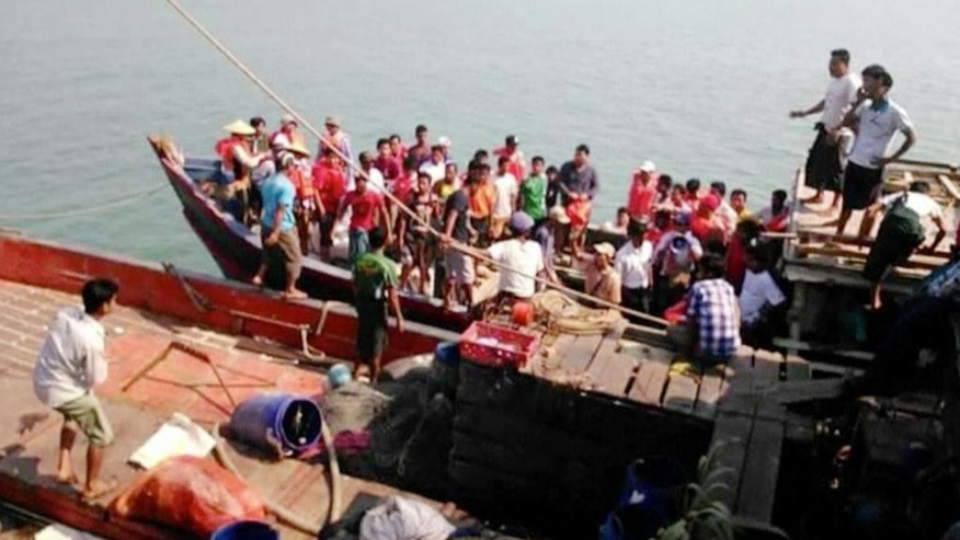 This image provided by DVB shows survivors who were saved after their ferry capsized near Kyauk Phyu port, Myanmar, on Saturday, March 14, 2015. A crowded double-decker ferry capsized in northwestern Myanmar after being slammed by huge waves, killing at least 21 people with nearly 50 others missing, officials said Saturday. (AP Photo/DVB) MANDATORY CREDIT
