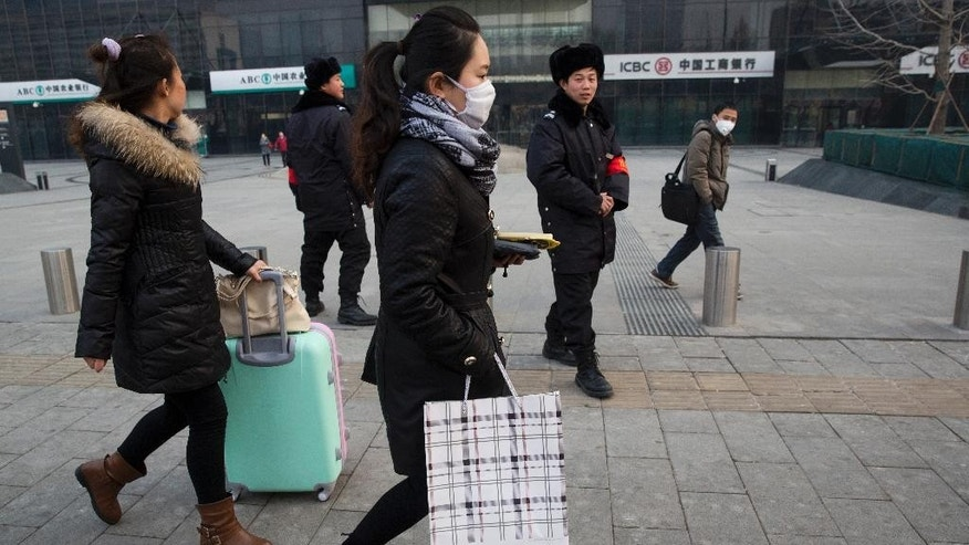 In this March 6, 2015 photo, residents wear masks for protection during a polluted day in Beijing. Since China launched a sweeping legal reform in January that toughens environmental penalties and allows more groups to sue polluters, Chinese have been rushing to test out the new laws and, in some cases, have taken industries to task for fouling their surroundings. (AP Photo/Ng Han Guan)