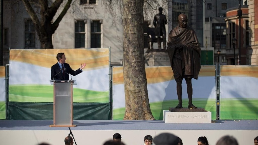 British Prime Minister David Cameron makes a speech next to a new statue of Mahatma Gandhi by British sculptor Philip Jackson after it was unveiled in Parliament Square, London, Saturday, March 14, 2015.  The bronze sculpture stands 9ft-high (2.75m) and will provide a focal point for commemorations of the 70th anniversary of Gandhi's death in 2018.  (AP Photo/Matt Dunham)
