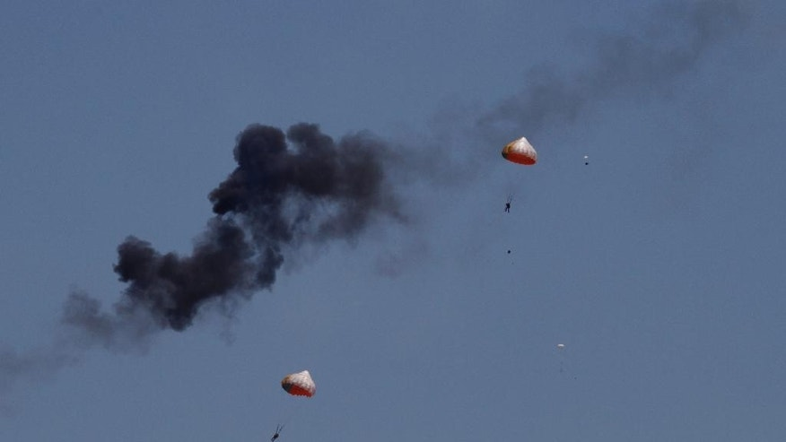 Pilots from Indonesia's Jupiter aerobatics team are ejected after a mid-air collision during a practice session at the Langkawi International Maritime and Aerospace (LIMA) exhibition in Langkawi, Malaysia, on Sunday, March 15, 2015. (AP Photo/Ow Eng Tiong)