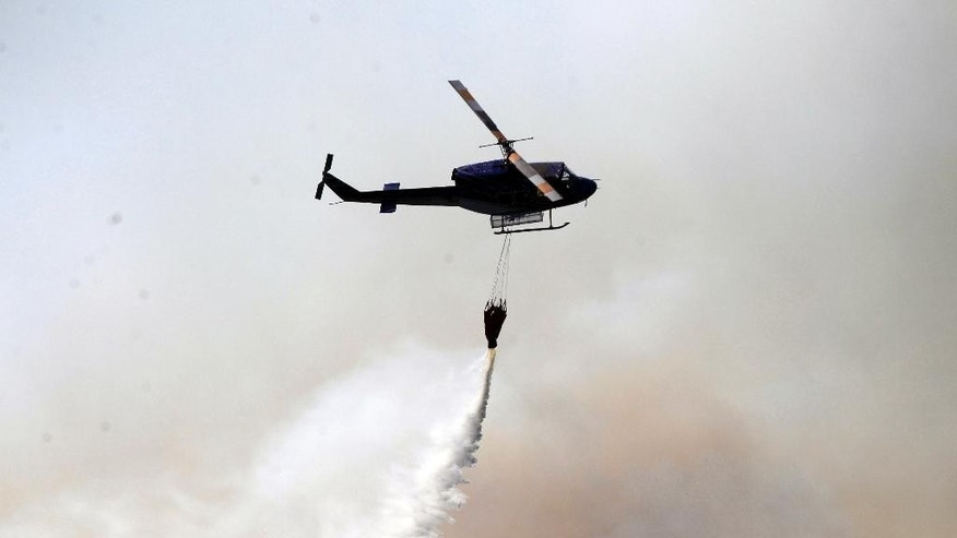A helicopter dumps water on a forest fire in Valparaiso, Chile, Saturday, March 14, 2015. A serious forest fire spread quickly on Chile's coast Friday and threatened to reach the nearby port cities of Valparaiso and Vina del Mar. (AP Photo/ Luis Hidalgo)
