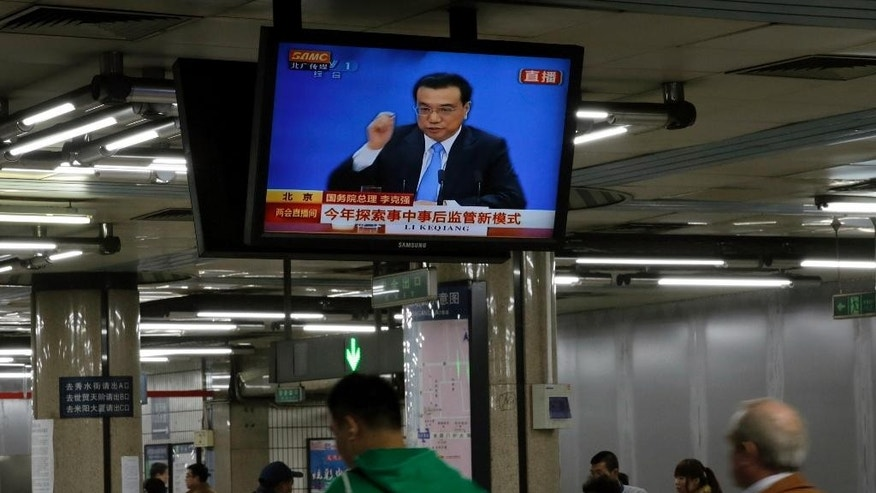 "Passengers walk past a TV showing a live broadcasting of Chinese Premier Li Keqiang who speaks at a press conference after the closing session of the annual National People's Congress, at a subway station in Beijing Sunday, March 15, 2015. Li expressed determination Sunday to press ahead with reforms meant to reduce the Chinese government's role in the economy in hopes of spurring growth despite what he acknowledged would be pain for ""vested interests"" that benefit from regulation. (AP Photo/Andy Wong)"