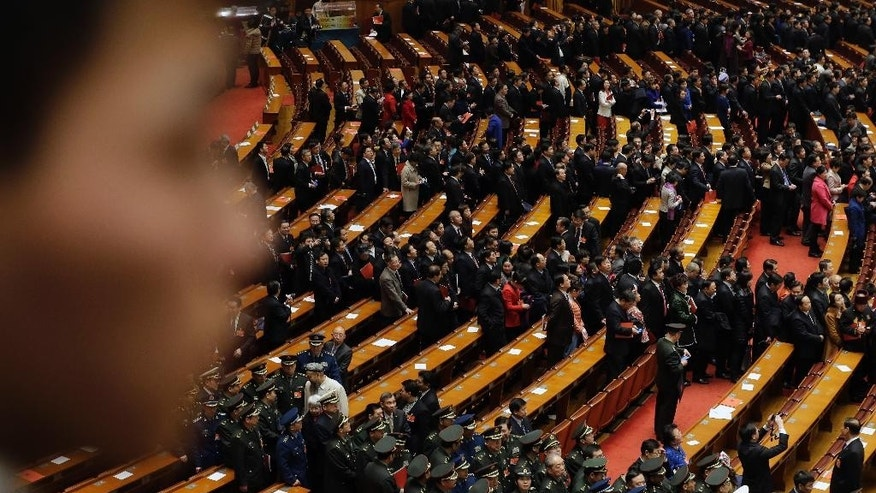 Delegates leave the hall after the closing session of the annual National People's Congress at the Great Hall of the People in Beijing Sunday, March 15, 2015. China's national legislature endorsed government plans Sunday to reduce the country's annual economic growth target from 7.5 to 7 percent before closing an annual session that also focused on maintaining employment levels, fighting corruption and curbing pollution. (AP Photo/Andy Wong)
