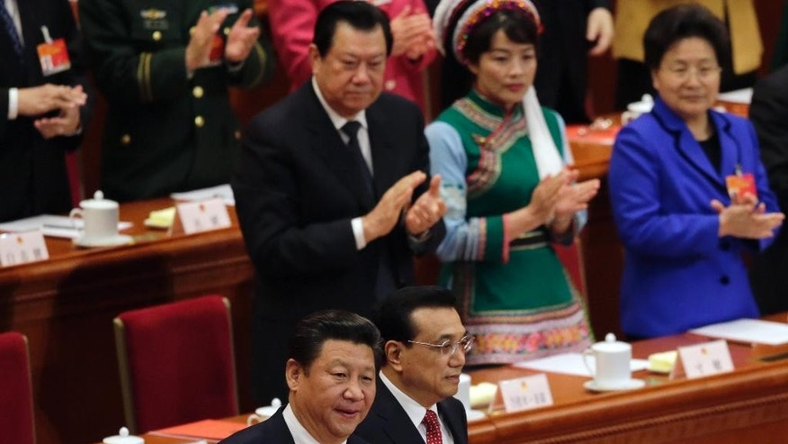 Delegates applaud as Chinese President Xi Jinping, bottom left, and Premier Li Keqiang, bottom right, arrive for the closing session of the annual National People's Congress at the Great Hall of the People in Beijing Sunday, March 15, 2015. China's national legislature endorsed government plans Sunday to reduce the country's annual economic growth target from 7.5 to 7 percent before closing an annual session that also focused on maintaining employment levels, fighting corruption and curbing pollution. (AP Photo/Andy Wong)