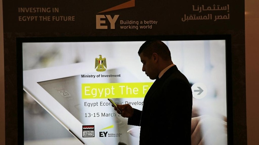 A delegate checks his phone at the venue for the Egyptian Economic Development Conference, a cornerstone of the government's plan to woo desperately needed investors, in Sharm el-Sheikh, Egypt, Sunday, March 15, 2015. (AP Photo/Thomas Hartwell)