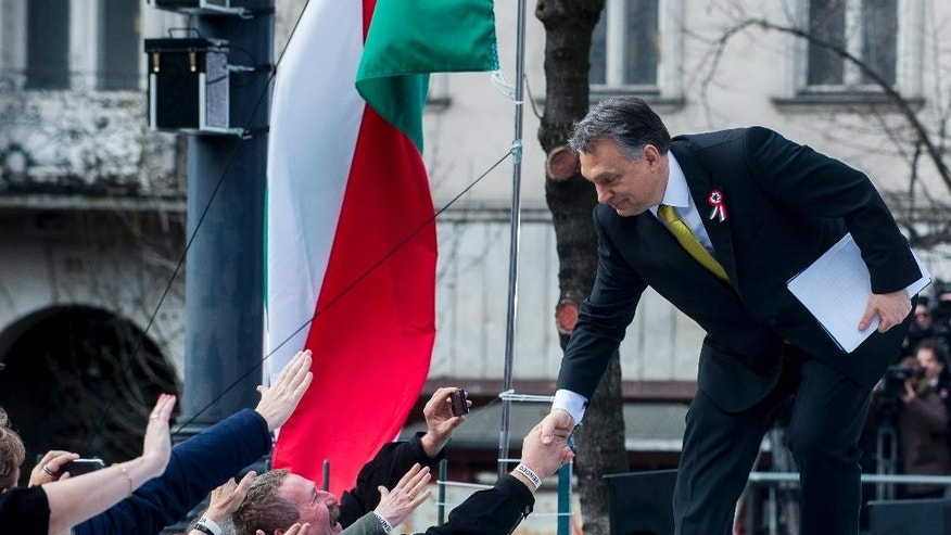 Hungarian Prime Minister Viktor Orban shakes hands with supporters after delivering his speech during commemorations of the 1848 uprising against the Hapsburg rule in Budapest, Hungary, Sunday, March 15, 2015. The speech by Orban was marred by scuffles between his supporters and a small group of opponents that were holding up posters and jeering Orban and his government _ accusing them of limiting civic rights. (AP Photo/MTI, Tamas Kovacs)