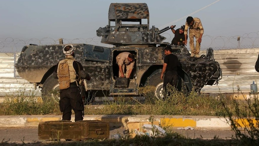Members of Iraqi Shiite militant group called Imam Ali Brigades prepare their armoured vehicle at the front line with Islamic State group in Tikrit, 130 kilometers (80 miles) north of Baghdad, Iraq, Saturday, March 14, 2015. Iraqi military officials have said they expect to reach the center of Tikrit within two to three days. (AP Photo/Khalid Mohammed)
