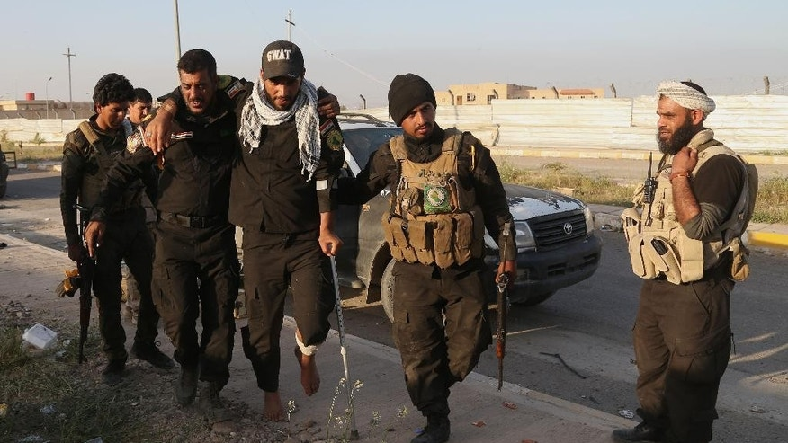 Members of Iraqi Shiite militant group called Imam Ali Brigades evacuate a wounded colleague outside the Qadisiyya neighborhood in Tikrit, 130 kilometers (80 miles) north of Baghdad, Iraq, Saturday, March 14, 2015. Iraqi military officials have said they expect to reach the center of Tikrit within two to three days. (AP Photo/Khalid Mohammed)