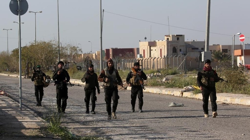 Members of Iraqi Shiite militant group called Imam Ali Brigades patrol outside Tikrit university in Tikrit, 130 kilometers (80 miles) north of Baghdad, Iraq, Saturday, March 14, 2015. Iraqi military officials have said they expect to reach the center of Tikrit within two to three days. (AP Photo/Khalid Mohammed)