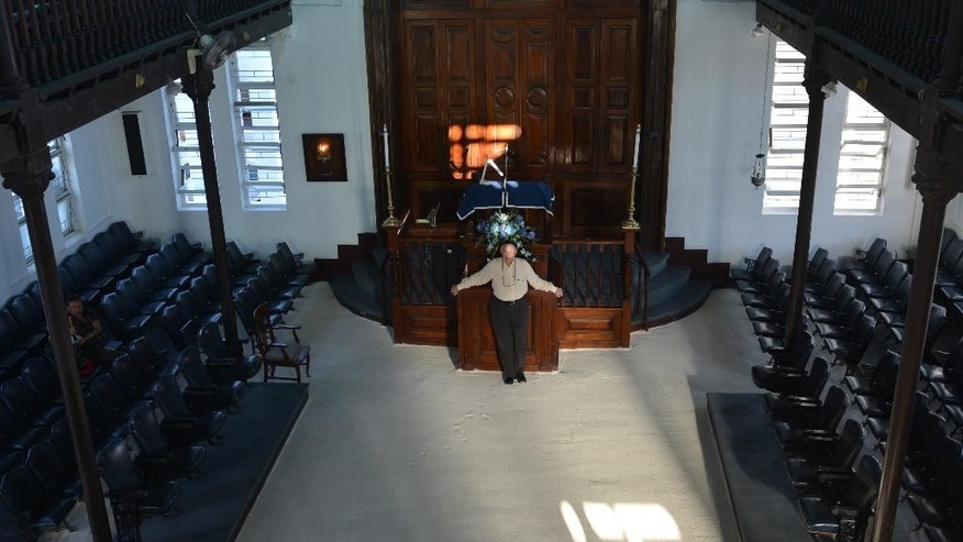 In this Feb. 27, 2015 photo, Jamaican Jewish community leader Ainsley Henriques poses for a photo on the sand covered floor of Sha'are Shalom, Jamaica's last synagogue, in Kingston. The dwindling congregation of the historic Kingston temple is trying to preserve their history and attract tourists who can appreciate it. In Jamaica in the 1800s, there were as many as eight synagogues and roughly 2,500 Jews, including quite a few who had a notable influence on civic life. (AP Photo/David McFadden)