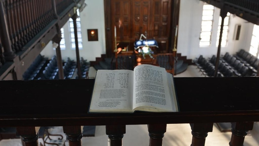 "In this Feb. 27, 2015 photo, a Hebrew prayer book with English translations is propped on a mahogany railing of the Sha'are Shalom, Jamaica's last synagogue, in Kingston. With most members of the congregation now over 50 years old, community members are trying to preserve their history and attract tourists who can appreciate it. The Jamaica Tourist Board says it's cultivating a ""Jewish Jamaica"" travel package as a form of ""heritage tourism"" that could encourage visitors to hold family celebrations such as weddings and bar and bat mitzvahs here. (AP Photo/David McFadden)"