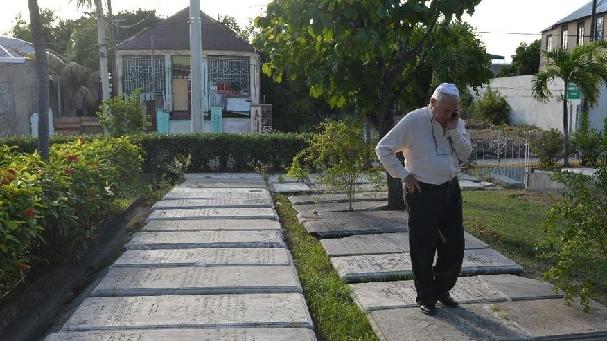 "In this Feb. 27, 2015 photo, Jewish community leader Ainsley Henriques walks on historic gravestones engraved with Hebrew inscriptions outside Jamaica's last synagogue, the Sha'are Shalom, in Kingston. ""Regardless of what happens in the future, I want people to always know that Jews were indeed here,"" said Henriques, who leads efforts to showcase the Jamaican community's traditions and draw visitors by hosting Jewish history conferences, opening a small museum next to the Kingston synagogue and trying to restore centuries-old Jewish cemeteries. (AP Photo/David McFadden)"
