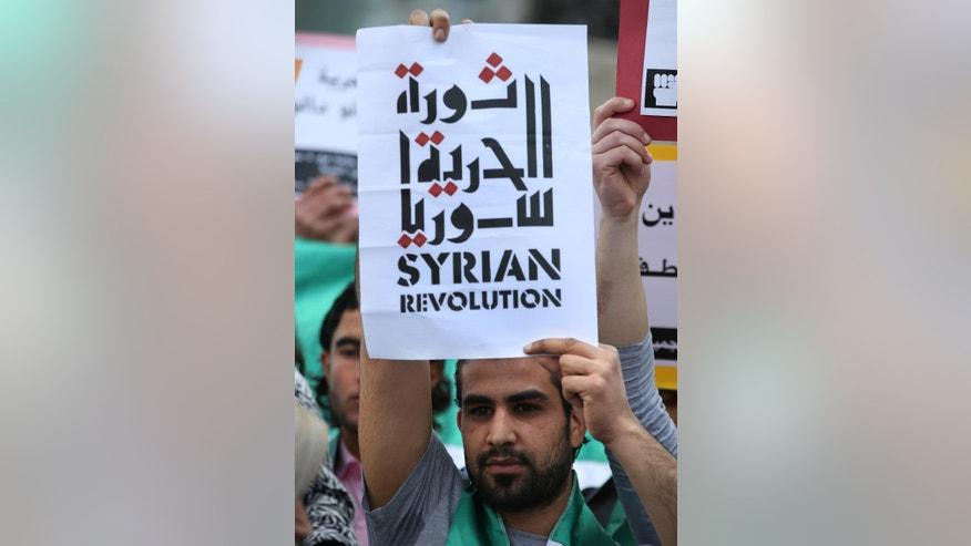 "An anti-Syrian government protester holds an Arabic placard that reads: ""The freedom Syrian revolution,"" as he attends a protest to mark the 4th anniversary of the Syrian uprising, at the Martyrs square in downtown Beirut, Lebanon, Sunday, March 15, 2015. Before the civil war started in March 2011, an estimated 22 million people lived in Syria. More than 3.8 million Syrians have fled their country in the four years since the uprising against President Bashar Assad began. (AP Photo/Hussein Malla)"