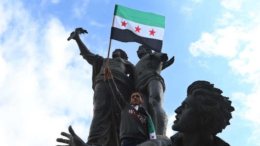 An anti-Syrian government protester waves the revolutionary flag, as he stands on the Lebanese Martyres statue during a protest to mark the 4th anniversary of the Syrian uprising, at the Martyrs square in downtown Beirut, Lebanon, Sunday, March 15, 2015. Before the civil war started in March 2011, an estimated 22 million people lived in Syria. More than 3.8 million Syrians have fled their country in the four years since the uprising against President Bashar Assad began. (AP Photo/Hussein Malla)