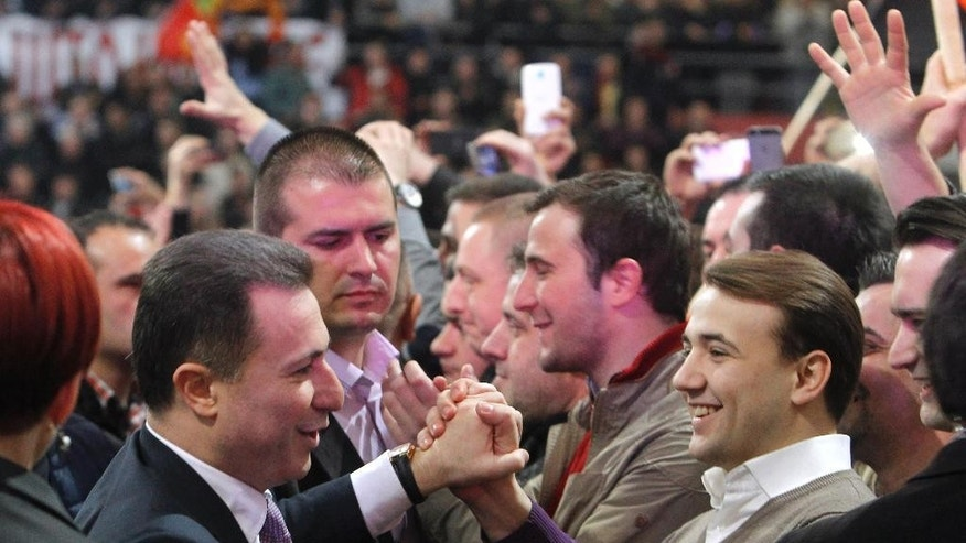 "Macedonian Prime Minister and leader of the ruling center-right VMRO-DPMNE party Nikola Gruevski, bottom left, is greeted by supporters on his arrival at the party's gathering in capital Skopje, Macedonia, Sunday, March 15, 2015. Prime Minister Gruevski said before thousands of supporters at the party's gathering on Sunday that he would not resign, adding that oppositional leader Zoran Zaev is working for ""foreign service interests"", by publishing illegally wire-taped recordings. (AP Photo/Boris Grdanoski)"
